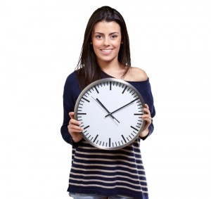 Smiling youthful woman holding a clock in front of her chest on a white background