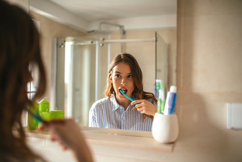 beautiful woman brushing teeth and looking in the mirror in the bathroom-img-blog