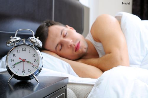 Man model sleeping with an alarm clock in foreground