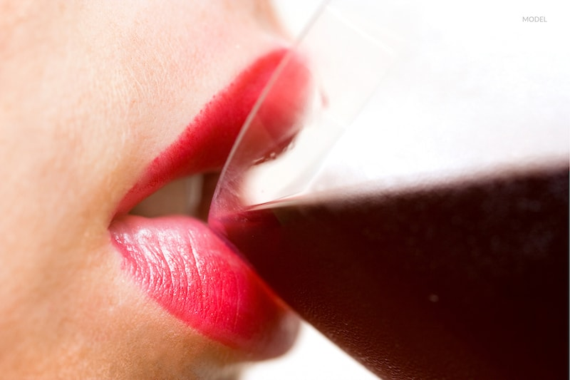 Close up of a woman drinking a glass of red wine.