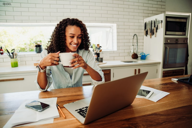 Woman with a white smile holding a cup of coffee looking at her laptop.