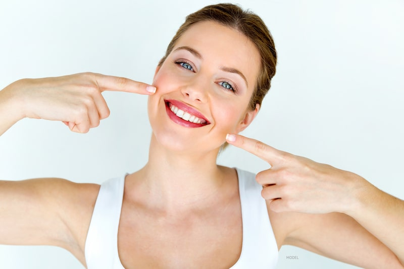 Smiling woman wearing white t-shirt, pointing at her white teeth.